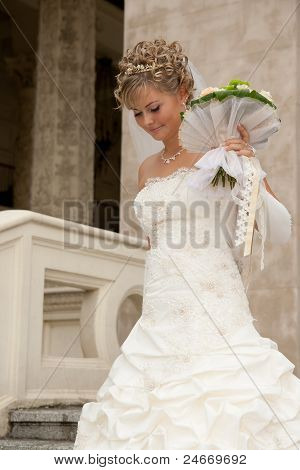 The Beutiful Bride With A Bouquet On The Steps Of Stone Stairs