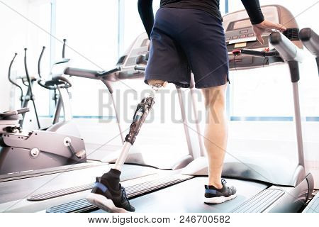 Low Angle Portrait Of Unrecognizable Muscular Man With Prosthetic Leg Using Walking On Treadmill Whi