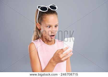 Unexpected message. Pleasant teenage girl being surprised by a text message from her friends, having read it from her smartphone poster