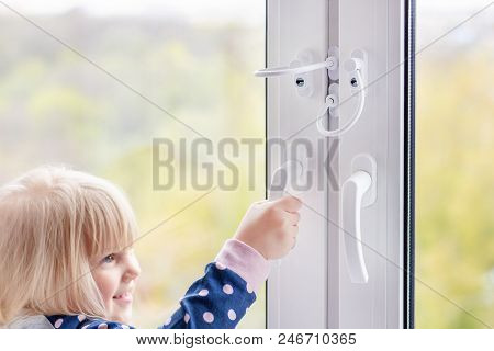 Little Cute Toddler Girl Trying To Open Window In Apartment At High-tower Building. Children Window