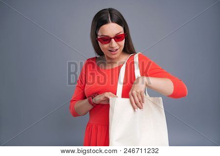 Fashion Icon. Attractive Dark-haired Woman In A Red Dress Wearing Red Glasses And Checking The Conte