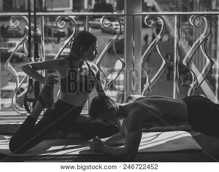 Sport And Gym Concept. Man And Woman In Sportswear In Gym, Window On Background. Couple Stretching O