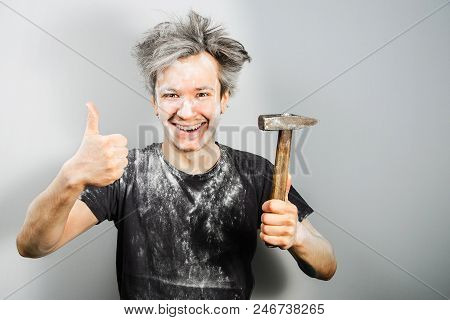 Unshorn In Construction Dust Young Guy Holds Hammer, Shows Thumb Up And Smiles, On Gray Background.