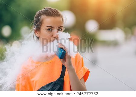Pretty Young Girl Vape Popular Ecig Gadget, Vaping Device.happy Brunette Vaper Girl With E-cig.portr