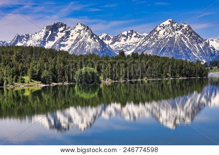 The Grand Tetons in Wyoming are reflected in the still waters of Jackson Lake.  This is a popular vacation destination in the Yellowstone and Jackson Hole areas.
