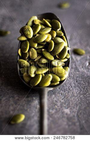Raw Pumpkin Seeds In Spoon On Rustic Dark Background