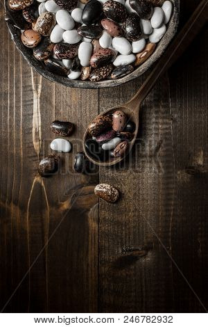 Colorful Raw Beans On Dark Wooden Background