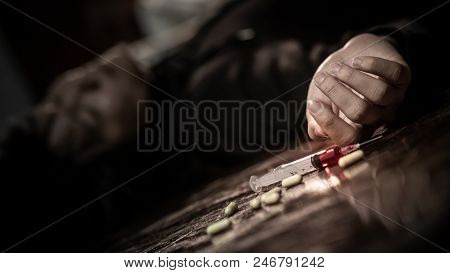 Junkie man lying on the fllor near drug injection syringe and pills. Death from drug overdose and addiction concept poster