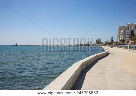 Cyprus, Larnaca city. Stone path around and above the sea. Harbor, beach, buildings, blue sky background.