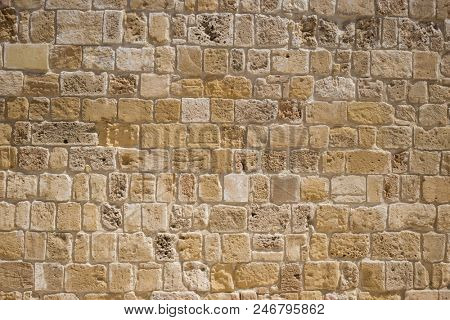 Sandstone, limestone aged wall at Cyprus. Yellow stonewall backdrop, close up view with details.