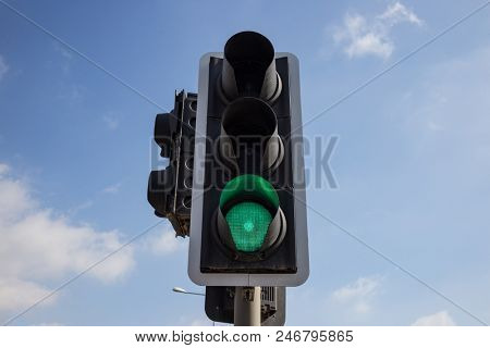 Green traffic light isolated. Signal that it is safe to go on the way. Blue sky with few clouds background. Close up under view.