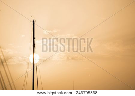 Yachts masts tops under Larnaca' s sky at sunset, sunrise with a circle sun. Pink sky background, space for text.