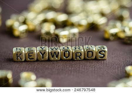 Word Keyword Made From Small Golden Letters On The Brown Background, Selective Focus