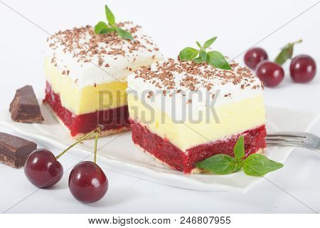 Sweet Homemade Cherry Cake With Vanilla And Whipping Cream On White Plate. Decorated With Chuks Of C