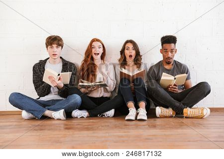 Image of shocked emotional young friends students sitting over white wall backgound indoors looking camera reading books.
