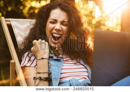 Photo of ecstatic brunette woman 18-20 clenching fist and screaming while sitting in deck chair during rest in park on sunny day and using silver laptop