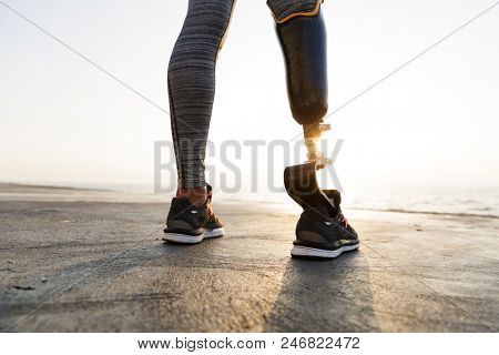 Close up back view of disabled athlete woman with prosthetic leg standing at the beach