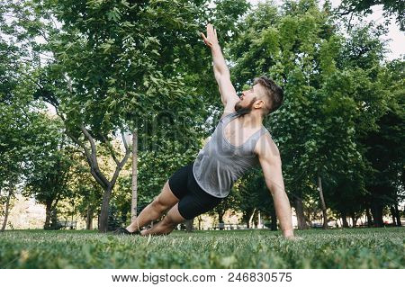 Yoga, endurance training, street workout, fitness, sport, outdoor activity, healthy lifestyle concept. Young fit muscular sportsman doing side plank in morning park poster