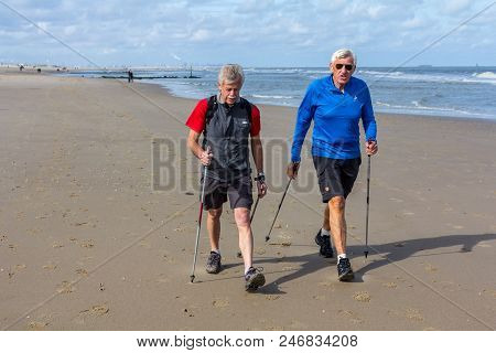 The Hague, The Netherlands - 24 June 2018: Senior Male Nordic Walkers Walking On Dutch Beach In Suns