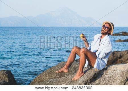 Young Man Eating Corn On The Beach