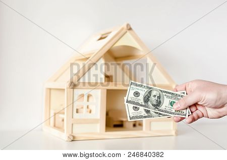 Hand Giving One Hundred Us Dollar Banknotes. Wooden House Model On Background. Real Estate Investmen