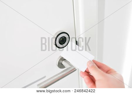 Hotel Door - Young Man Holding A Keycard In Front Of The Electronic Sensor Of A Room Door.