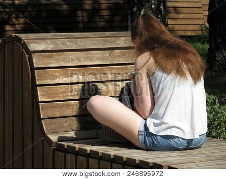 Slim Girl In Jeans Shorts Sitting On The Wooden Bench With A Smartphone In A Park. Concept For Commu