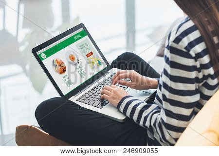 Asian Woman Cross Leg Sitting At Couch Use Laptop To Order Food Online In Website At Home.digital Le
