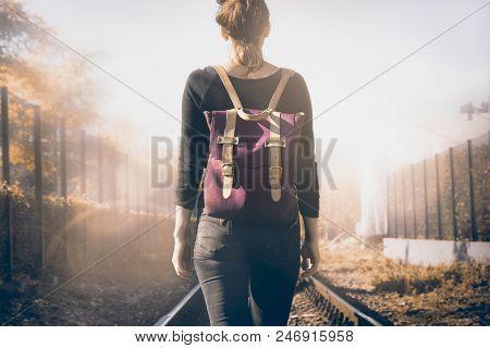 Traveler girl walking on railway tracks. Lonely traveler girl. Traveler. Traveler girl walking in sunshine. Travel concept. Backpack traveler.