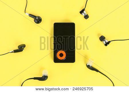 Mp3 Player With Headphones On Pastel Yellow Background. Minimalism