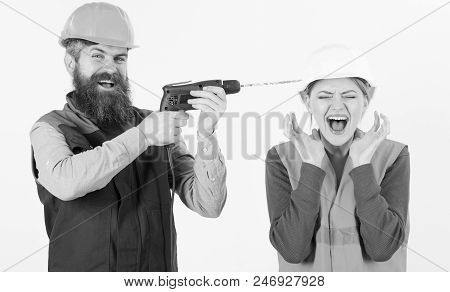 Husband Annoying His Wife. Annoying Repair Concept. Man With Happy Face Drills Head Of Woman, White
