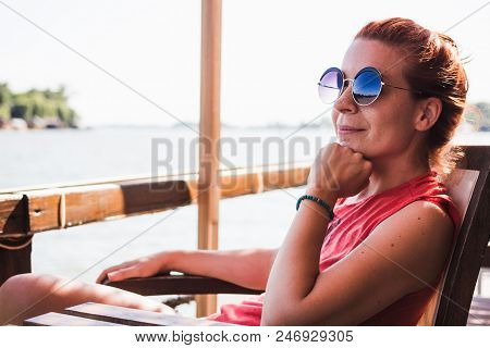 Young Woman Sitting In A Cafe By The River