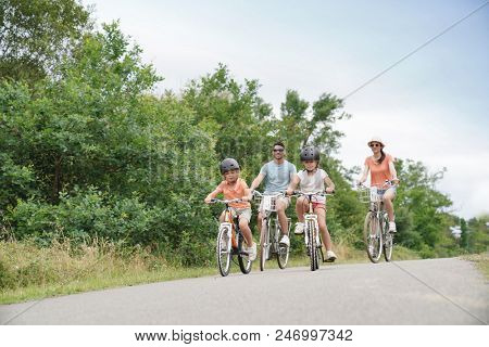 Kids with parents riding bikes in countryside
