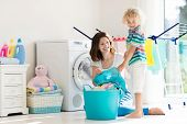 Mother and kids in laundry room with washing machine or tumble dryer. Family chores. Modern household devices and washing detergent in white sunny home. Clean washed clothes on drying rack. poster