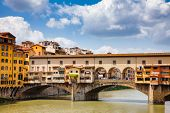 Picturesque Ponte Vecchio (Old Bridge) medieval bridge with Vasari Corridor (Corridoio Vasariano) elevated enclosed passageway  over the Arno River, a popular tourist attraction of  Florence, Tuscany poster