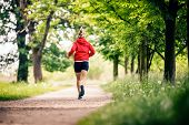 Running woman, enjoying summer day in park. Endurance training, jogging or power walking female athlete, physical activity concept outdoors. poster