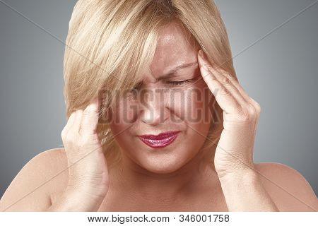 A Tired Upset Middle-aged Woman Suffers From Severe Chronic Headache, Migraine, Dizziness, During Me