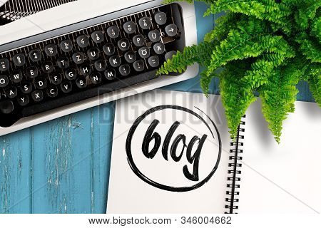 Blogging Concept, Top View Of Old Typewriter, Potted Plant And Notepad With Word Blog On Wooden Tabl