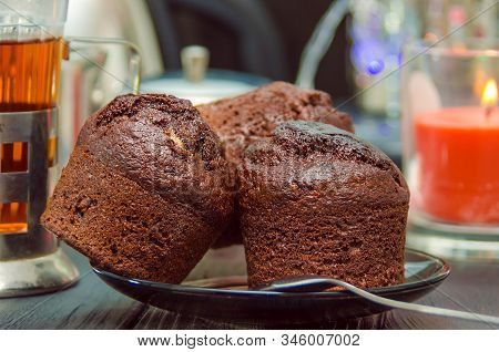 Chocolate Muffins On Wooden Background With Tea Glass In Iron Cup Holder. Homemade Chocolate Cakes.