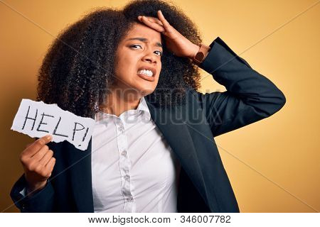 Young african american business woman with afro hair holding help paper for work stress stressed with hand on head, shocked with shame and surprise face, angry and frustrated. Fear and upset