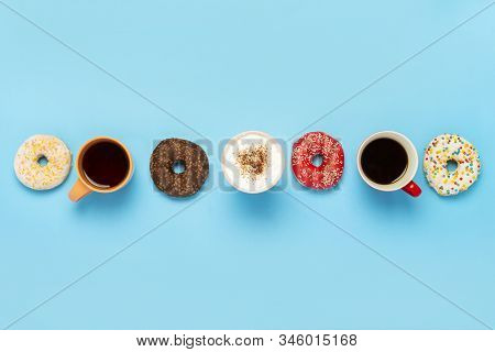 Tasty Donuts And Cups With Hot Drinks, Coffee, Cappuccino, Tea On A Blue Background. Concept Of Swee