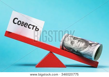 The Inscription In Russian: Conscience. A Sheet Of Paper And Money On A Swing. Social Injustice Conc
