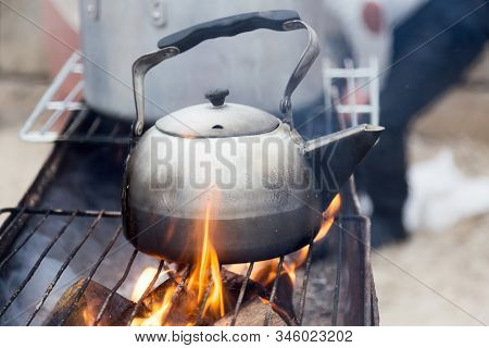 Old Hot Kettle Antique Bonfire With Particles With Flames. Old Aluminum Kettle On Bonfire. Iron Kett