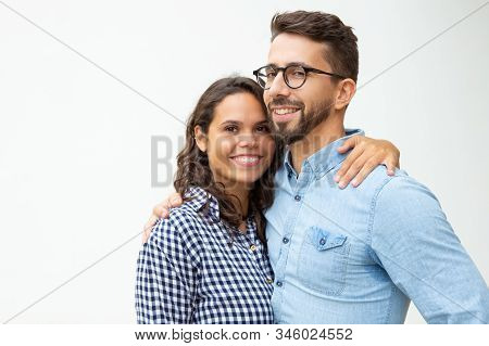 Happy Young Couple Standing And Embracing. Beautiful Cheerful Young Couple Hugging And Smiling At Ca