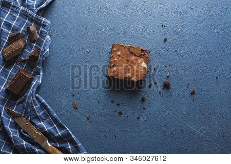 Last Piece Of Brownie On Blue Table With Crumbs, Napkin, And Chocolate Chunks. Above View Of One Cho