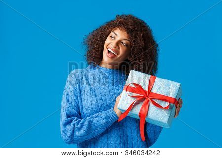 Curious And Excited Happy Young African American Woman Shaking Present To Guess Whats Inside, Standi