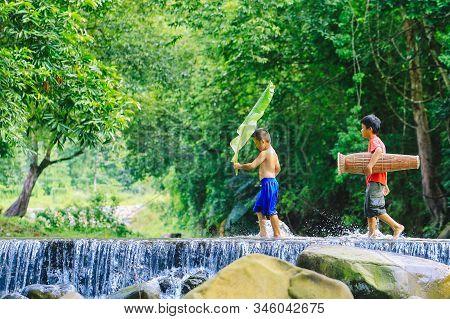 Penampang,sabah,malaysia-oct 29,2016:kadazan Dusun Kids With Bamboo Fish Trap In The River At Penamp