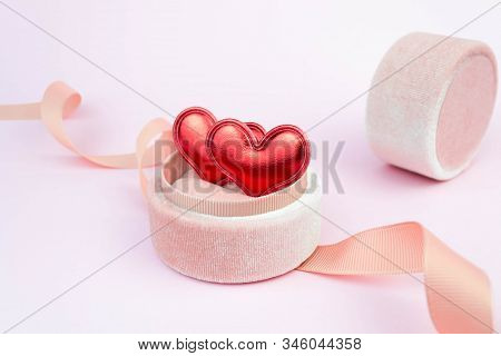 Two Red Hearts In A Ring Box With Ribbon On Soft Pink Background. Love Feelings Confession. Romantic