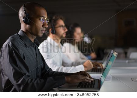 Side View Of Concentrated Call Center Operator Working. Thoughtful Call Center Operators During Work
