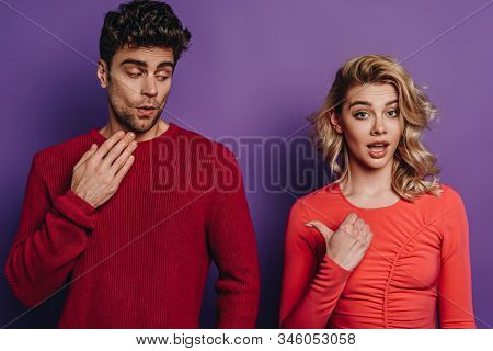 Shocked Girl Pointing With Thumb At Discouraged Boyfriend On Purple Background